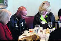 Dallas Police Chief David Brown and City Manager Mary Suhm prayed during Wednesday's breakfast meeting of the North Texas Crime Commission. Brown told the gathering that he had been unaware of the decision to add a police escort for his son's funeral procession.