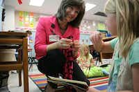 First-grade teacher Pam Taylor of Garden Ridge Elementary helps a student with headphones for audio accompanying a book.Staff photo by DANIEL HOUSTON  -  neighborsgo