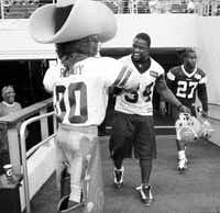 Cowboy Deon Anderson got stopped on his way to the field by team mascot Rowdy on Tuesday during the open practice at Cowboys Stadium. Team officials say they haven't seen a decrease in the demand for tickets.