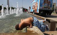 Eight-year-old Coby Vandergriff dunks his head in a Fair Park fountain Thursday after attending the annual Dallas Mayor's Back to School Fair. Temperatures were expected to reach 109 degrees Thursday, making it the fourth straight day of record highs and the 34th straight day above 100 degrees in Dallas-Fort Worth.