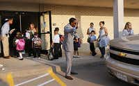 Solomon Adair, Uplift Grand Preparatory middle school dean, helps the traffic flow Tuesday as students arrive for the first day of classes at the new Uplift Grand Preparatory School in Grand Prairie. Classes started Tuesday for almost 10,000 students spread across charter school operator Uplift Education's 13 Dallas-Fort Worth campuses.(David Woo - Staff Photographer)