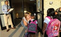 Emily Huggins of Uplift Grand Preparatory school greets students arriving Tuesday for the first day of classes at Uplift Education's new campus in Grand Prairie. Classes started Tuesday for 12,000 students spread across the charter school operator's 14 Dallas-Fort Worth campuses.(David Woo - Staff Photographer)