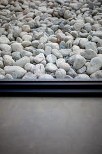 Glass separates the concrete-floor interior from the garden's tumbled rock.