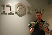 Nerve Software founder and president Brandon James holds up some of the popular game titles such as Return to Castle Wolfenstein and Call of Duty: Black Ops that the company has worked on over the years.
