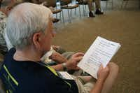 """Monty Huffington reads along with other group members for a vocal exercise during a Loud Crowd session at the Parkinson Voice Project's new facility off Coit Road. The group called the """"12 Angry Men"""" is one of nine Loud Crowd groups that meet weekly."""