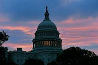 The sun rises behind the US Capitol building on Oct. 17, the morning after the House and the Senate passed a bipartisan bill to reopen the government and raise the debt limit.JEWEL SAMAD - AFP/Getty Images