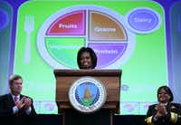 Michelle Obama, Agriculture Secretary Tom Vilsack and Surgeon General Regina Benjamin unveil the new food icon.(Alex Wong)