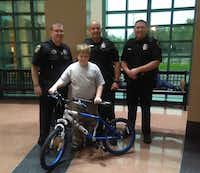 Irving police Officers Craig Holman (left), Kyle Chaisson and Rawley Miller with Jonathan and his new bike. (Tina Merimon/Facebook)