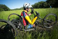 """Brown rides a custom-made, three-wheeled bike that he propels, steers and brakes essentially with one arm. Bush called the Warrior 100K's camaraderie """"just wonderful.""""Paul Morse"""