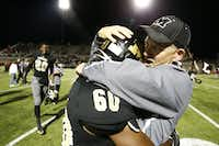 A Mansfield's coach hugs Ju'Nathean McAllister after their game against Cedar Hill at Vernon Newsom Stadium  in Mansfield, Texas October 29, 2015. Mansfield won the game 46-43 (Nathan Hunsinger The Dallas Morning News)(The Dallas Morning News)