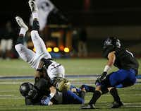 Plano East wide receiver Cameron Moore (14) is tackled by Hebron defensive back Colton Chapin (8) after making a reception in the third quarter during a high school football game between Plano East and Hebron at Hawk Stadium in Carrollton, Texas Thursday October 29, 2015. Plano East beat Hebron 21-14. (Andy Jacobsohn/The Dallas Morning News)(The Dallas Morning News)