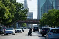 A man wheels a trash can on Main Street in Deep Ellum as I-345 passes overhead in the back ground, dividing Deep Ellum from downtown Dallas on June 17, 2016. (Ting Shen/The Dallas Morning News)