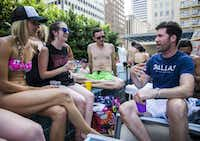 Craig Smith (right) talks with Nikki Smith (left), Lindsay Manley and Mario Marquez (center) during a pool party at the Mercantile Place apartment building where they live on Saturday, June 18, 2016 at 1800 Main Street in downtown Dallas. Smith is a student at UNT Dallas College of Law and walks across the street to his classes. (Ashley Landis/The Dallas Morning News)
