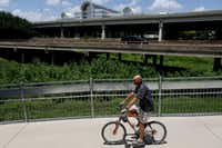 A cyclist rides west along the Trinity Strand Trail's eastern terminus with Interstate 35, near Oak Lawn Ave. in the Design District neighborhood east of I-35E (elevated, background) as the Infomart is seen in the background across the highway in Dallas Tuesday June 22, 2016.(Andy Jacobsohn/The Dallas Morning News)