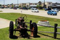 An old tractor is a reminder of yesteryear, displayed along Hwy. 380 in the retail strip including Walmart, Starbucks and numerous other stores, in the small Denton County town of Cross Roads, Texas, Wednesday, June 8, 2016.(Tom Fox/Staff Photographer)