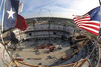 <p>The Texas and American flags flew from the top of the tower crane at the 50 yard line of the Cowboys' AT&T Stadium under construction in 2007.</p>(File Photo/Tom Fox)