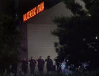 Dallas police officers stood in salute as fallen officers were transported into UT Southwestern vans through a secure entrance at Parkland Memorial Hospital in Dallas early Friday.(Rose Baca, Staff Photographer)