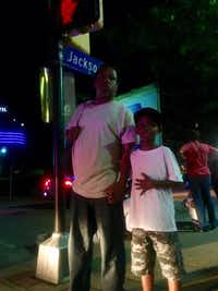 Kevin Thomas and his 7-year-old son, Kevin Thomas Jr., hold hands on a Dallas street corner.(Sarah Mervosh/Staff)