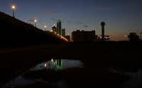 """<p><span style=""""font-size: 1em; line-height: 1.364; background-color: transparent;"""">Reunion Tower (right) stood with the lights out as the sun rose over downtown Dallas on Friday. Many Dallas businesses turned out their lights to honor the police killed and wounded in Thursday night's attack.</span></p>(The Associated Press)"""