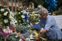 A woman places flowers at a memorial outside the Dallas police headquarters.   (Laura Buckman/Agence France-Presse)