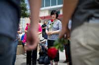 Tae Hee Yoon, of Carrollton, prays with other members of the Semihan Korean Baptist Church in Carrollton, Texas by the memorial for the slain officers at the Dallas Police headquarters on Saturday.Ting Shen/The Dallas Morning News