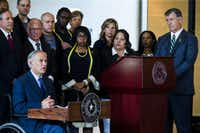 Texas Gov. Greg Abbott (left) and Dallas Mayor Mike Rawlings (right) speak during a press conference on Friday at Dallas City Hall in downtown Dallas, Texas. They stood in front of a group of Dallas city councilmen, state representatives, state senators and Texas Attorney General Ken Paxton (standing on far left). They made comments about a shooting on Thursday in downtown Dallas that targeted police officers and left five people dead and seven more injured.(Ashley Landis/The Dallas Morning News)