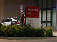 A Dallas police officer stands guard at the emergency room entrance to Parkland Hospital after a shooting that left 10 officers shot and three dead during a Black Lives Matter rally in downtown Dallas on July 7, 2016. (Rose Baca/The Dallas Morning News)