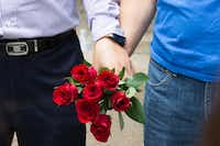 Injae Chang, and Bon Ku, pastors from the Semihan Korean Baptist Church in Carrollton, Texas hold hands carrying roses in prayer in front of the memorial for the slain officers at the Dallas Police Headquarters on July 9, 2016 in Dallas. (Ting Shen/The Dallas Morning News)(The Dallas Morning News)