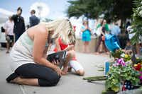 Christie Pressly, 35, of Jonesboro, Arkansas, prays in front of the memorial for the slain officers at the Dallas Police Headquarters on July 9, 2016 in Dallas. (Ting Shen/The Dallas Morning News)(The Dallas Morning News)