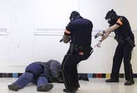Dallas police officer Stanley Stokely, left, plays an angry man with a knife as Sr. Cpl. Perry Strickland, center, and Sr. Cpl. Daniel Ek draw their guns during a staged reality-based training drill in November. (David Woo/ Dallas Morning News)(<p><br></p><p></p>)