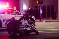 A Dallas officer took cover behind a police motorcycle during the sniper attack. (Smiley N. Pool/Staff Photographer)