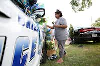 Rosa Marez places a cross on a squad car memorial at the Dallas Police Department's Southwest Patrol Division in Dallas on Saturday.(Rose Baca/Staff Photographer)