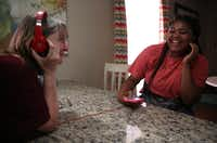 Resident Ebonie Jones (right) laughs at Ebby House Program Director Lisa Mumford's reaction to the music she is listening to.(Rose Baca/Staff Photographer)