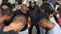 Protesters, counterprotesters and a Dallas police officer pray together at the end of a demonstration in July near NorthPark Center. (Hannah Wise/Staff)