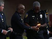 Dallas Area Rapid Transit Police Chief James Spiller (right) lights Chief David Brown's candle during Monday night's vigil at Dallas City Hall. At left is Dallas Police Association President Ron Pinkston.(Nathan Hunsinger/The Dallas Morning News)