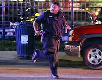 A Dallas Police Department officer runs for cover during the chaos that followed a deadly shooting  Friday, July 7, 2016 in Dallas. As a Black Lives Matter protest wound down, a gunman opened fire, shooting 11 police officers, killing five of them.(G.J. McCarthy/Staff Photographer)