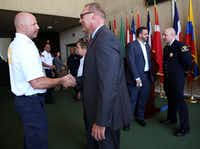 New Dallas Fire Chief David Coatney (right) shook hands with Battalion Chief Cameron Creager after a news conference announced Coatney's new position at Dallas City Hall in June. Coatney started his new job on Wednesday.&nbsp;(<p><br></p><p>Rose Baca/The Dallas Morning News</p><p></p>)
