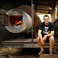 Famed pitmaster Aaron Franklin poses with his smoker behind Franklin Barbecue in 2013 on Day 2 of the Texas BBQ Posse's Best of Texas BBQ Tour.(Tom Fox/Staff Photographer)