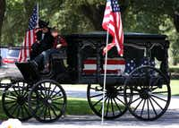 <p>Magnus Ahrens, 8, son of fallen Dallas police Senior Cpl. Lorne Ahrens sits with the driver of a caisson bearing his father's casket during Ahrens' burial service.</p>(<p>(Rose Baca/The Dallas Morning News)</p>)