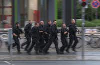 In this grab taken from video, police run in the area of the Olympia Einkaufszentrum mall, after a shooting, in Munich, Germany, Friday, July 22, 2016. A manhunt was underway Friday for a shooter or shooters who opened fire at a shopping mall in Munich, killing and wounding several people, a Munich police spokeswoman said. The city transit system shut down and police asked people to avoid public places. (AP)(AP)