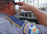 (A Baton Rouge police officer saluted the family of slain East Baton Rouge sheriff's Deputy Brad Garafola on Saturday. (Jae S. Lee / Staff Photographer))