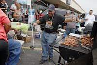 Elvin Torres, 33, of the Latin American Motorcycle Association, dances to Puerto Rican music as he cooks on a grill during the <i>chinchorreo</i>.(Ben Torres/Special Contributor)