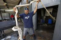 Fernando Grimaldo pulls a hose to fill up his neighbor Stephen Nevil's water tank at Nevil's house, which is located in an unincorporated area of southeastern Dallas County. (Jae S. Lee/Staff Photographer)