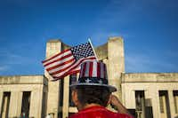 Bob Crawford waved the flag while listening to the Dallas Winds perform in front of the Hall of State during the Fair Park Fourth celebration.((Smiley N. Pool/The Dallas Morning News))