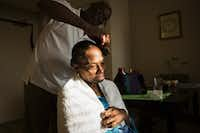 """<p>Herbert fixes his wife's hair at their apartment in Dallas. """"He's a part of my life that I've always been missing: someone to love me, care for me and abide me,"""" Laura said.</p>(Smiley N. Pool/Staff Photographer)"""