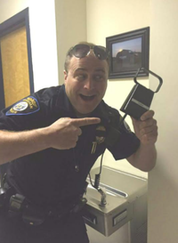 Officer Ernest MacVane shows off a cowbell after he tried to arrest the two cows on a Maine road.(Windham Police Department )