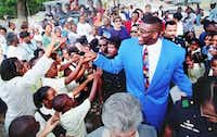 Larry Johnson of the Charlotte Hornets greets fans and well-wishers as he arrives for a ceremony in his old neighborhood of Dixon Circle in Dallas on Sept. 6, 1995. (AP)