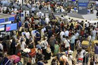 Passengers swarm the check-in counter for Delta Air Lines at Narita international airport in Narita, east of Tokyo, on Tuesday. More than 1,000 people were forced to spend the night at Tokyo's Narita airport because of the computer shutdown that halted Delta Air Lines flights worldwide. (AP Photo/Shizuo Kambayashi)