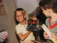 Brad Hunstable holds up a digital clock radio he got for his 8th birthday in 1986. Brad taught himself to use computers and went on to co-found Ustream, a pioneer in live video streaming. (Courtesy of Fred Hunstable)