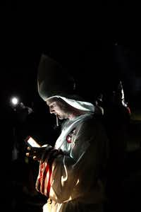 "In this Saturday, April 23, 2016 photo, a member of the Ku Klux Klan uses a mobile device during cross burnings after a ""white pride"" rally in rural Paulding County near Cedar Town, Ga. (<p><span style=""font-size: 1em; line-height: 1.364; background-color: transparent;"">AP Photo/John Bazemore</span><br></p><p></p>)"